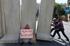 """A Lebanese man holds a placard with Arabic that reads, """"I swear it feels like I'm at the border with Israel,"""" as an engineering unit installs a concrete wall near the main Lebanese government building, a day after a violent anti-government protests, in downtown Beirut, Lebanon, Monday, Aug. 24, 2015. Organizers of the """"You stink"""" protests that have captivated the Lebanese capital postponed anti-government demonstrations set for Monday evening after a night of violent clashes with police during which dozens of protesters and police officers were wounded. (AP Photo/Hassan Ammar)"""