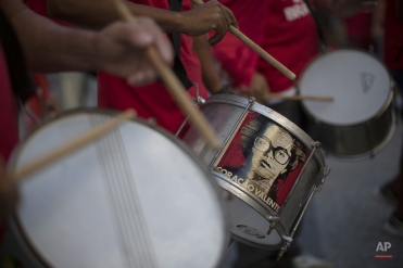 """With a sticker of Brazil's President DIlma Rousseff on the center drum that reads in Portuguese """"Brave Heart,"""" demonstrators play drums during a march in support of president Rousseff in Rio de Janeiro, Brazil, Thursday, Aug. 20, 2015. Demonstrators marched in several cities across the nation to show support for Rousseff, after the recent Petrobras corruption scandal in which Brazil's Attorney General's has filed charges against Chamber of Deputies speaker Eduardo Cunha and Sen. Fernando Collor. Rousseff, who's pole numbers are at an all time low, has not been accused of any wrongdoing, although she served as chairwoman of the Petrobras board during several years as the scheme played out. (AP Photo/Leo Correa)"""