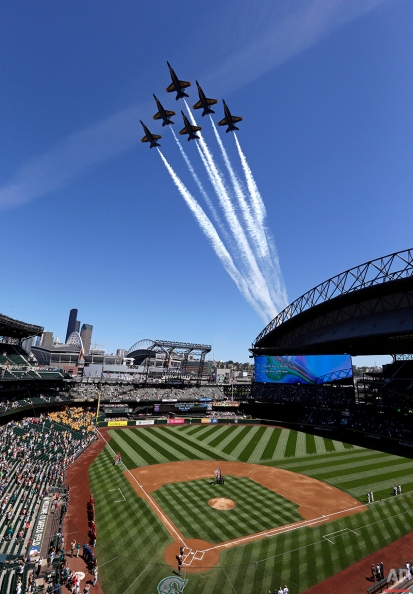 Members of the U.S. Navy Blue Angels fly in formation over the Seattle Mariners' ballpark, Safeco Field, before a baseball game against the Arizona Diamondbacks Wednesday, July 29, 2015, in Seattle. The Blue Angels will perform at Seafair Weekend over Lake Washington Friday through Sunday. (AP Photo/Elaine Thompson)