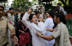A policewoman, right, tries to stop an opposition Congress party supporter from approaching the residence of a senior leader of the ruling Bhartiya Janta Party during a protest against rising prices of onion and other food items in New Delhi, India, Tuesday, Aug. 25, 2015. The prices of onion, a staple food of the Indian middle class, have been soaring in the past weeks leading to protests. (AP Photo/Altaf Qadri)