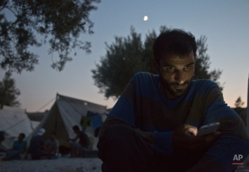 A Syrian migrant looks at his mobile phone in the Kara Tepe refugee camp near the town of Mytilene on the southeastern Greek island of Lesbos, Greece, Thursday, Aug. 20, 2015. Greece this year has been overwhelmed by record numbers of migrants arriving on its eastern Aegean islands, with more than 160,000 landing so far. (AP Photo/Visar Kryeziu)