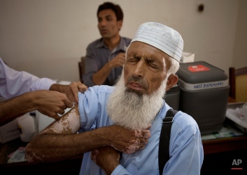 A Pakistani volunteer gives vaccine shot to a pilgrim at Hajj Complex in preparation to travel to Saudi Arabia to perform Hajj, Friday, Aug. 21, 2015 in Islamabad, Pakistan. A total of 143,000 Pakistanis will be performing the pilgrimage this year. In order to facilitate the pilgrims, the government of Pakistan makes requisite arrangements, including the set-up of Special Vaccination Camps for Pilgrims in light of the travel requirements set down by the government of Saudi Arabia. (AP Photo/B.K. Bangash)