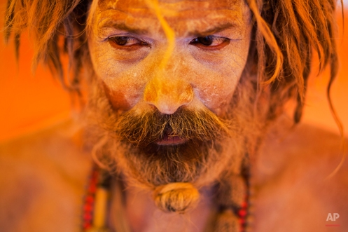 A Naga sadhu, or naked Hindu holy man, pauses inside a tent during Kumbh Mela, or Pitcher festival, at Trimbakeshwar, India, Thursday, Aug. 27, 2015. Hindus believe taking a dip in the waters of a holy river during the festival will cleanse them of their sins. The festival is held four times every 12 years. (AP Photo/Bernat Armangue)