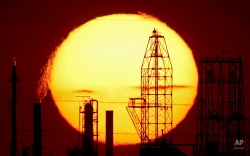 The National Cooperative Refinery Association oil refinery is silhouetted against the setting sun Wednesday, Aug. 19, 2015, in McPherson, Kan. (AP Photo/Charlie Riedel)
