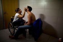 Argentine dancer Gabriela Fernanda Torres, left, puts makeup on her partner Pablo Rafael Pereyra as they prepare to compete in the stage category in the World Tango Championship, in Buenos Aires, Argentina, Friday, Aug. 21, 2015. Paralyzed in a car accident when she was 2 years old, Torres says she has no memories without her wheelchair. The 37-year-old began dancing as a child and is now a member of the Dance Company Without Borders, an integrated dance program. (AP Photo/Natacha Pisarenko)