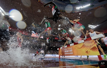 Kenya's Ezekiel Kemboi, centre, takes the water jump on his way to winning the gold medal in the menís 3000m steeplechase final at the World Athletics Championships at the Bird's Nest stadium in Beijing, Monday, Aug. 24, 2015. (AP Photo/Andy Wong)