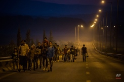 Syrian refugees walk along the roads of the border town of Idomeni , northern Greece to cross the border and enter Macedonia, on Tuesday Aug. 25, 2015. The U.N.ís refugee agency said it expects 3,000 people to cross Macedonia daily in the coming days. Greece has been overwhelmed this year by record numbers of migrants who have been arriving on a number of Greek islands.(AP Photo/Santi Palacios)