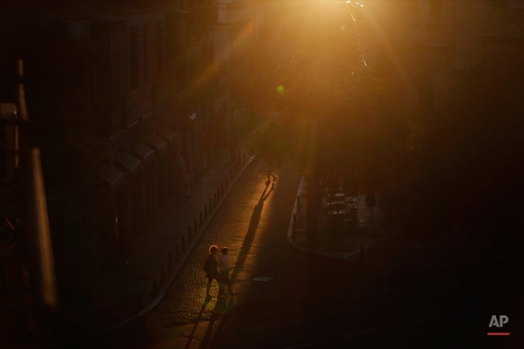 People cast their shadows against a cobble-stoned street, as they walk in Madrid's Malasana neighbourhood, Spain, Monday, Aug. 24, 2015. The quarter, located in the Spanish capital city center, is a lively area full of restaurants, pubs and clothes shops. (AP Photo/Francisco Seco)