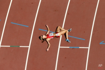 United States' Nicole Tully lays on the track after completing a round one heat of the women's 5000m at the World Athletics Championships at the Bird's Nest stadium in Beijing, Thursday, Aug. 27, 2015. (AP Photo/Wong Maye-E)