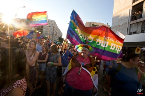 People carry flags during a Gay Pride parade before an ultra-Orthodox Jew stabbed several people with a knife in Jerusalem on Thursday, July 30, 2015. Yishai Schlissel, an ultra-Orthodox Jewish man, lunged into a group of revelers at the annual gay pride parade and stabbed several of them as they marched in the holy city. (AP Photo/Sebastian Scheiner)