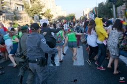 Israeli security forces reach for ultra-Orthodox Jew Yishai Schlissel attacking people with a knife during a Gay Pride parade Thursday, July 30, 2015 in Jerusalem. (AP Photo/Sebastian Scheiner)