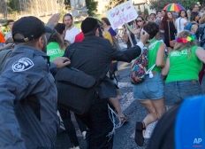 An ultra-Orthodox Jew stabs a woman in the back with a knife during a Gay Pride parade Thursday, July 30, 2015 in central Jerusalem. Israeli police said several people were stabbed. (AP Photo/Sebastian Scheiner)
