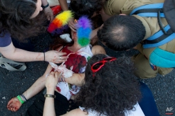 Paramedics help a wounded woman after an ultra-Orthodox Jew attacked people with a knife during a Gay Pride parade Thursday, July 30, 2015 in Jerusalem. (AP Photo/Sebastian Scheiner)