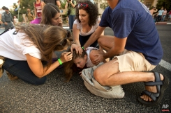People help a wounded person after Yishai Schlissel, an ultra-Orthodox Jew, attacked people with a knife during a gay pride parade in Jerusalem on Thursday, July 30, 2015. (AP Photo/Sebastian Scheiner)