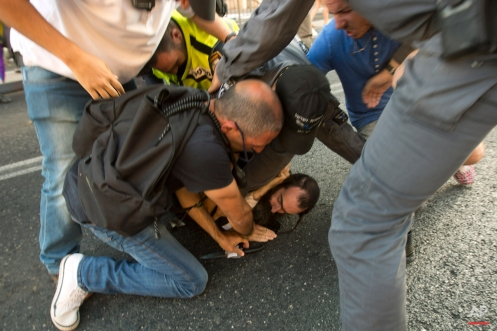 A police officer removes a knife from ultra-Orthodox Jew Yishai Schlissel after he stabbed people during a gay pride parade in Jerusalem on Thursday, July 30, 2015. (AP Photo/Sebastian Scheiner)