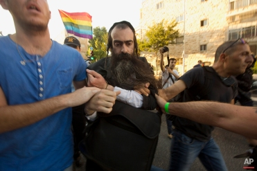 Ultra-Orthodox Jew Yishai Schlissel is detained by plain-clothes police officers after he stabbed people during a gay pride parade Thursday, July 30, 2015 in Jerusalem. (AP Photo/Sebastian Scheiner)