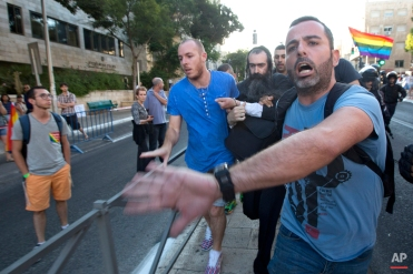 Plainclothes Israeli police detain an ultra-Orthodox Jew after he attacked people with a knife during a Gay Pride parade Thursday, July 30, 2015 in Jerusalem. (AP Photo/Sebastian Scheiner)