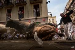 Revelers run chased by 'El Tajo y La Reina' ranch fighting bulls as they turn Estafeta corner during a running of the bulls of the San Fermin festival in Pamplona, Spain. (AP Photo/Daniel Ochoa de Olza)