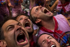 Revelers open their mouthes as they wait to cool off with water thrown from a balcony to celebrate the official opening of the 2015 San Fermin Fiestas, in Pamplona, northern Spain, July 6, 2015. (AP Photo/Andres Kudacki)