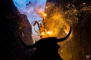"""A flaming fake bull known as a """"Toro de fuego"""" runs after revelers during San Fermin festival in Pamplona, Spain, Monday, July 13, 2015. (AP Photo/Andres Kudacki)"""