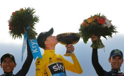 Britain's Chris Froome, center, kisses the trophy as he stands on the podium with second placed Colombia's Nairo Quintana, left, and Spain's Alejandro Valverde at the end of the Tour de France cycling race in Paris, France, Sunday, July 26, 2015. (AP Photo/Christophe Ena)