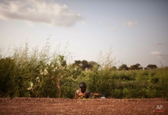 A Burkina Faso government soldier takes cover as he and others patrol a suburb taking control from the soldiers that took part in a coup in Ouagadougou, Burkina Faso. Tuesday, Sept. 29, 2015. Burkina Faso's army stepped up the pressure Tuesday against those behind last weekís short-lived coup, surrounding the barracks of coup plotters and arresting a former high-ranking minister accused of collaborating with the mutinous soldiers. (AP Photo/Theo Renaut)