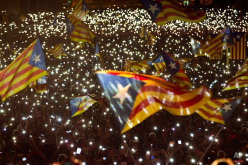 """Pro independence supporters wave """"estelada"""" or pro independence flags during a rally of """"Junts pel Si"""" or """"Together for YES"""" in Barcelona, Spain, Friday, Sept. 25, 2015. Catalans vote Sunday in regional parliamentary elections that the breakaway camp hopes will give them a mandate to put their region on a path toward independence - a goal the Madrid central government says would be illegal. (AP Photo/Emilio Morenatti)"""