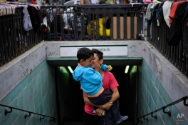 An Afghan boy kisses his brother as they exit from a metro station at Victoria square, where many stay temporarily before trying to continue their trip to more prosperous northern European countries, in Athens, Wednesday, Sept. 23, 2015. The 28-nation EU took a modest step toward dealing with the issue by agreeing to relocate 120,000 asylum-seekers to ease the strain on Greece and Italy, which are on the front line of the migrant flood. (AP Photo/Fotis Plegas G.)