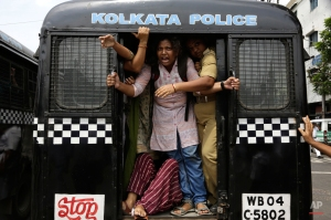 An activist of Socialist Unity Center of India shouts slogans as she is detained by the police in a van during a daylong nationwide strike called by the trade unions in Kolkata, India, Wednesday, Sept. 2, 2015. Normal life was affected in various parts of the country, including the West Bengal state, as central trade unions on Wednesday went on a day-long nationwide strike to protest against changes in labour laws and privatization of Public Sector Undertaking's (PSU), a government owned corporation. (AP Photo/Bikas Das)