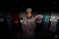 Rohingya refugees, an ethnic persecuted Muslim minority fleeing Myanmar, a predominantly Buddhist nation, pray at their slum on the outskirts of New Delhi, India, Thursday, Sept. 3, 2015. According to the United Nations refugee agency (UNHCR), there are around 9,000 Rohingya registered in the capital with thousands more unregistered ones living in different parts of the country. In Delhi, most of them lead impoverished lives in tented settlements dotted around the city. (AP Photo/Tsering Topgyal)
