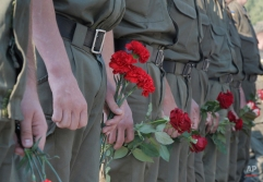Ukrainian soldiers wait for their turn to pay the last tribute to a coffin bearing the body of National Guard soldier Igor Derbin who was killed in a Monday clash, at a military base in Novi Petrivtsi outside Kiev, Ukraine, Wednesday, Sept. 2, 2015. Ukrainian police say 141 people remain hospitalized after a nationalist protest in Kiev turned violent, with 10 of the injured in serious condition. Three officers died from their wounds. (AP Photo/Efrem Lukatsky)