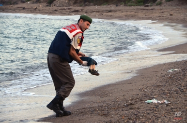 A paramilitary police officer carries the lifeless body of a migrant child after a number of migrants died and a smaller number were reported missing after boats carrying them to the Greek island of Kos capsized, near the Turkish resort of Bodrum early Wednesday, Sept. 2, 2015. (AP Photo/DHA)