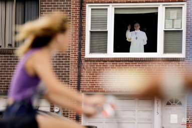 A woman cycles past a home displaying a cutout of Pope Pope Francis after his weekend visit, Tuesday, Sept. 29, 2015, in Philadelphia. City and Catholic leaders on Monday heralded Pope Francis' weekend visit as a success while acknowledging complaints from pilgrims who got stuck in long security lines and businesses that saw underwhelming demand. (AP Photo/Matt Rourke)
