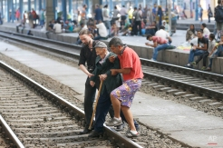 Migrants help an elderly man to cross tracks at the railway station in Budapest, Hungary, Thursday, Sept. 3, 2015. Over 150,000 migrants have reached Hungary this year, most coming through the southern border with Serbia, and many apply for asylum but quickly try to leave for richer EU countries.(AP Photo/Frank Augstein)
