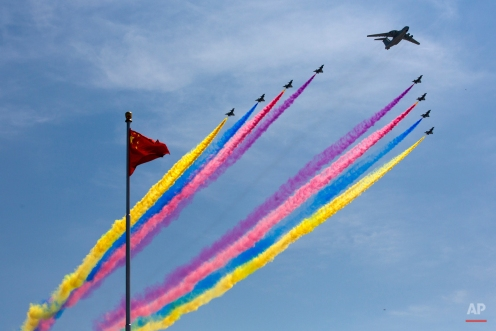 A KJ-2000 airborne early warning and control system leads J-10 fighter jets flying past a national flag during a military parade to commemorate the 70th anniversary of Japan's World War II defeat in Beijing Thursday, Sept. 3, 2015. The spectacle involved more than 12,000 troops, 500 pieces of military hardware and 200 aircraft of various types, representing what military officials say is the Chinese military's most cutting-edge technology. (AP Photo/Andy Wong, Pool)