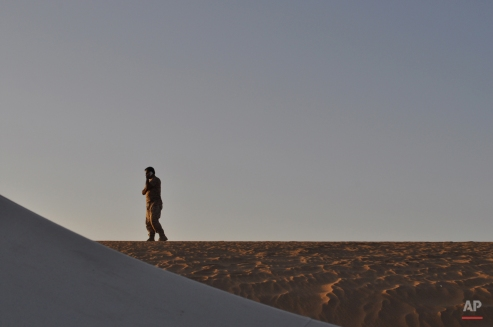 United Arab Emirates Brig. Gen. Ali Saif al-Kaabi talks on a phone atop a sand dune at a United Arab Emirates military base near Saffer, Yemen, Monday, Sept. 14, 2015. As fighting rages on in Yemen, troops from the United Arab Emirates that are part of a Saudi-led coalition battling Shiite rebels are pushing toward the country's rebel-held capital, Sanaa, after securing a strategic provincial city, the commander of an Emirati contingent said Monday. (AP Photo/Adam Schreck)