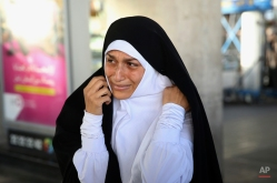 An Iranian hajj pilgrim gets emotional upon her relative's arrival at Tehran Imam Khomeini airport, Iran, Tuesday, Sept. 29, 2015. More than 700 pilgrims were killed on Thursday in a stampede during the final days of the annual hajj in Mina near the holy city of Mecca, Saudi Arabia. The disaster killed at least 239 Iranian pilgrims, while over 200 people remain missing, Iran's state television reported. (AP Photo/Vahid Salemi)
