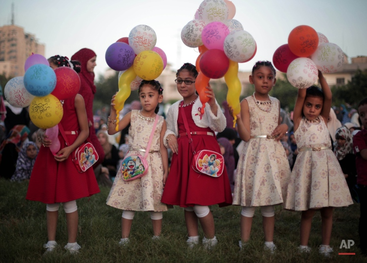 Palestinian girls hold balloons as they celebrate the first day of Eid al-Adha in Gaza City, Thursday, Sept. 24, 2015. Muslims will slaughter cattle and goats later, with the beef and meat distributed to the needy in the holiday which honors the prophet Abraham for preparing to sacrifice his son on the order of God, who was testing his faith. (AP Photo/ Khalil Hamra)