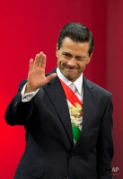 Mexico's President Enrique Pena Nieto winks and waves as he acknowledges invited guests before delivering his third State of the Nation address, inside the National Palace in Mexico City, Wednesday, Sept. 2, 2015. Pena Nieto sent his written report to Congress on Tuesday in an atmosphere of rising violence, a falling currency and a slowing economy. (AP Photo/Rebecca Blackwell)