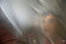 Jackson Gabriel, 6, looks through a curtain during an occupation of the Saint Peter by homeless families, in Brasilia, Brazil, Monday, Sept. 14, 2015. About 500 families from the People's Resistance Movement are asking the local government to meet the housing demands for families. (AP Photo/Eraldo Peres)