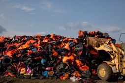 An excavator works on a huge pile of life vests and dinghies that have been used by migrants at a local dump of the island of Lesbos, Greece, Thursday, Sept. 24, 2015. More than 260,000 asylum-seekers have arrived in Greece so far this year, most reaching the country's eastern islands on flimsy rafts or boats from the nearby Turkish coast.(AP Photo/Petros Giannakouris)