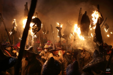 Villagers dress up in old clothes and cover their heads as they take part in The Civic procession of el Vitor in the town of Mayorga in Valladolid, Spain, Monday, Sept. 28, 2015. Villagers from a small village in the northern Spain burn leather wineskins that are hung from poles and between the songs of worshipers, the cloud of smoke, the fire and the smell of burnt fish pays homage to Santo Toribio, a missionary native to the village of Mayorga who was canonised in the 18th century. These acts of devotion are held in memory of the day that the villagers received the remains of the saint, in whose name the people went into the streets with flaming torches and lanterns. (AP Photo/Jose Vicente)