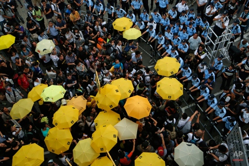 "Protesters holding yellow umbrellas gather to observe a moment of silence to mark the first anniversary of ""Umbrella Movement"" outside the government headquarters in Hong Kong, Monday, Sept. 28, 2015. A year ago, Hong Kong's famously busy streets were shut down by pro-democracy activists who occupied them for 79 days in what became known as the ""Umbrella Movement."" The protests were led by students and other activists who took to the streets to voice their opposition against Beijing's plan to restrict elections for top leader of the semiautonomous Chinese city. (AP Photo/Kin Cheung)"