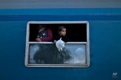 A Syrian refugee child holds a balloon fashioned from a glove while waiting with her family in a train heading for the Austrian border, in Roszke, southern Hungary, Monday, Sept. 14, 2015. Hungary is set to introduce much harsher border controls at midnight ó laws that would send smugglers to prison and deport migrants who cut under Hungary's new razor-wire border fence. The country's leader was emphatically clear that they were designed to keep the migrants out. (AP Photo/Muhammed Muheisen)