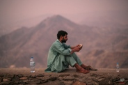 A Muslim pilgrim reads the holy Muslim book Quran on his mobile phone atop Noor Mountain outside the Hiraa cave, where Prophet Muhammad received his first revelation from God to preach Islam, on the outskirts of Mecca, Saudi Arabia, Friday, Sept. 18, 2015. Hajj is expected to start on Monday. More than 1 million pilgrims have already arrived for the annual pilgrimage, which all able-bodied Muslims are required to perform once in their lives. (AP Photo/Mosa'ab Elshamy)