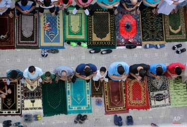 Egyptians pray Eid al-Adha prayers outside al-Seddik mosque in Cairo, Egypt, Thursday, Sept. 24, 2015. Muslims all over the world celebrate the three-day festival Eid al-Adha, by sacrificing sheep, goats, camels and cows to commemorate the willingness of the Prophet Ibrahim (Abraham to Christians and Jews) to sacrifice his son, Ismail, on God's command. (AP Photo/Amr Nabil)