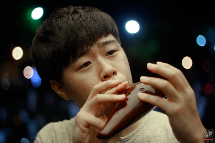 """In this Aug. 14, 2015, photo, Kim Myung, 23, plays the ocarina, a flute-like instrument, in Samcheong-dong, Seoul, where he often busks to cope with his feelings since he defected from North Korea to the South in 2006. When he reunited with his mother after a perilous, three-year-long escape, she was busy working in South Korea and left him alone at home. Kim met his first love when he went to a Korean public bathhouse in 2006. """"Back then I didn't know the word, 'gay,' or what it was conceptually. I just wanted to be his friend and feel the warmth that I missed from my mom,"""" Kim said. (AP Photo/Julie Yoon)"""