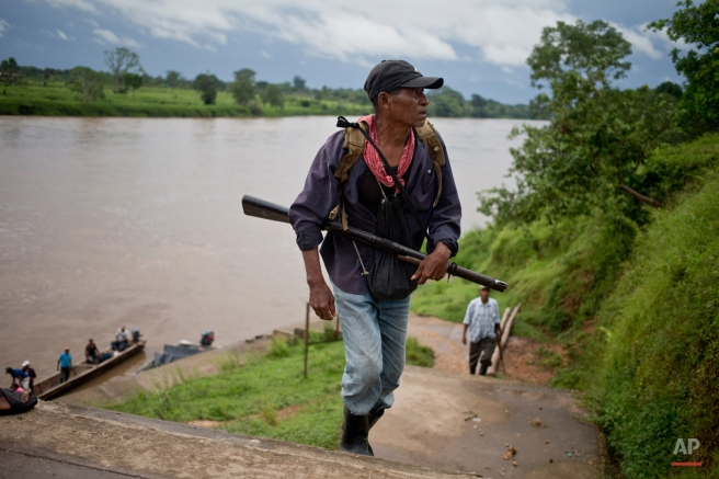 In this Sept. 19, 2015 photo, a Miskito man arrives after taking part in a defense patrol, in La Esperanza, Nicaragua. Miskito men who are resisting the arrival of settlers patrol the humid terrain wearing knee-high boots, and armed with crude weapons - double-pronged fishing spears, knives, machetes, bows and arrows. But some carry rifles they say they seized from invaders. (AP Photo/Esteban Felix)
