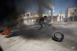 A Palestinian burns tires during clashes with Israeli troops at Qalandia checkpoint between Jerusalem and the West Bank city of Ramallah, Friday, Sept. 18, 2015. Palestinian protesters continued clashing with Israeli security forces on Friday in various parts of the West Bank and east Jerusalem. Israeli troops fired tear gas, stun grenades and deployed a water cannon to disperse stone-throwing Palestinian youths. Friday's clashes follow days of unrest at Jerusalem's hilltop compound known to the Muslims as the Noble Sanctuary and to Jews as the Temple Mount. (AP Photo/Majdi Mohammed)