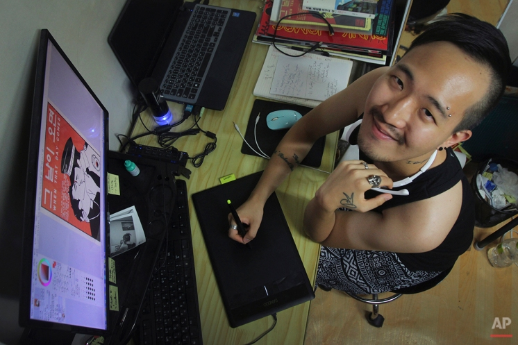 """In this Aug. 6, 2015, photo, Heezy Yang, 25, poses for a photograph in his home in Hapjeong-dong, Seoul, South Korea. Before coming out in 2013, Yang hid his sexuality because """"that was the normal way to live a life in (South) Korea."""" He now juggles multiple jobs: graphic novelist, LGBT rights activist and Korean language tutor. """"No matter how conservative this country is, you will always find a way and be able to live and have friends if you try,"""" he said. (AP Photo/Julie Yoon)"""
